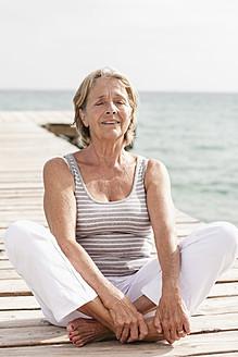 Spain, Senior woman doing yoga on jetty at the sea - JKF000048