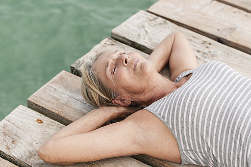 Spain, Senior woman relaxing on jetty at the sea - JKF000051