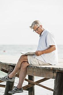 Spain, Senior man reading newspaper on jetty at the sea - JKF000054
