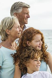 Spain, Grandparents with grandchildren atthe sea - JKF000057