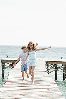 Spain, Girl and boy running on jetty at he sea - JKF000072