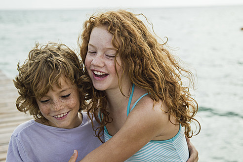 Spain, Girl and boy at the sea, smiling - JKF000075