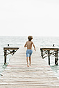 Spain, Boy running on jetty at the sea - JKF000078