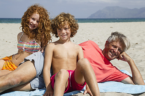 Spain, Grandfather and grandchildren relaxing on beach, smiling - JKF000098