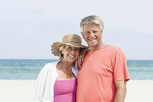 Spain, Senior couple standing at beach, smiling, portrait - JKF000110