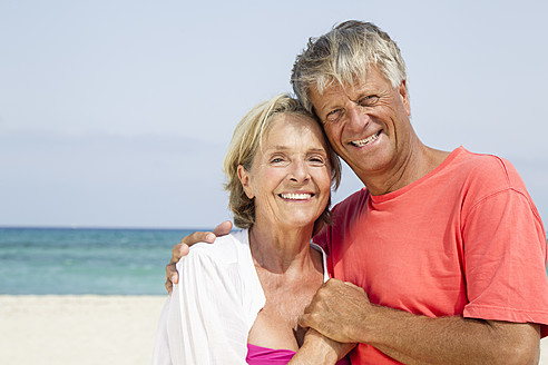 Spain, Senior couple standing at beach, smiling, portrait - JKF000113