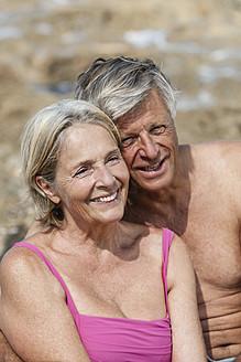 Spain, Senior couple sitting on rock at beach, smiling - JKF000122