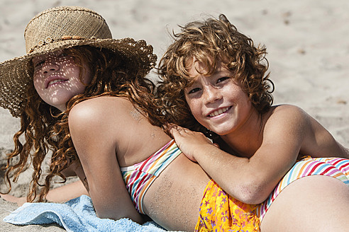 Spain, Brother and sister having fun on beach - JKF000125