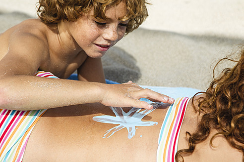 Spain, Brother drawing on sisters back with suncream - JKF000128