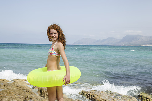 Spain, Girl with swim ring on beach, smiling - JKF000137