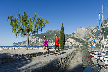 Italy, Mid adult couple jogging by Lake Garda - MIRF000513