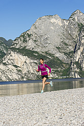 Italy, Mid adult woman jogging by Lake Garda - MIRF000519