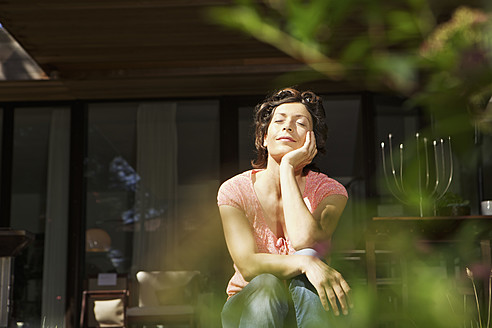 Germany, Berlin, Mature woman relaxing on terrace - SKF001101
