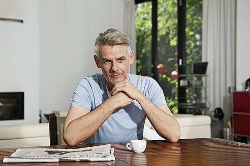 Germany, Berlin, Mature man sitting at table, portrait - SKF001107
