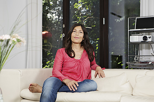 Germany, Berlin, Mature woman sitting on couch, smiling, portrait - SKF001110