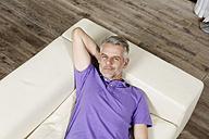 Germany, Berlin, Mature man lying on sofa, smiling, portrait - SKF001131