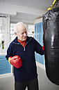 Germany, Duesseldorf, Senior man with boxing glove and punch bag - STKF000089