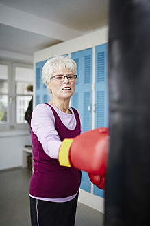Germany, Duesseldorf, Senior woman with boxing glove and punch bag - STKF000093