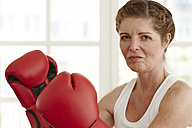 Germany, Duesseldorf, Portrait of mature woman with boxing gloves - STKF000103