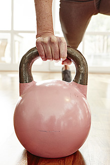 Germany, Duesseldorf, Mature woman exercising with kettlebell - STKF000108