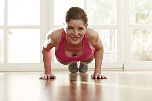 Germany, Duesseldorf, Mature woman doing push ups at home - STKF000113