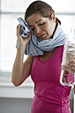 Germany, Duesseldorf, Mature woman drying face after exercise - STKF000143