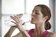 Germany, Duesseldorf, Mature woman drinking water after exercise - STKF000147