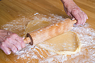 Human hand kneading dough with rolling pin, close up - ABAF000564