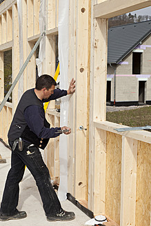 Europe, Germany, Rhineland Palatinate, Man installing and fixing wooden walls of prefabricated house - CSF016038