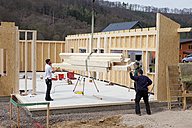 Europe, Germany, Rhineland Palantinate, Men installing and fixing wooden walls of prefabricated house - CSF016014