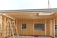 Europe, Germany, Rhineland Palatinate, Man installing and fixing wooden walls of prefabricated house - CSF016053