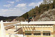 Europe, Germany, Rhineland Palantinate, Man installing and fixing wooden walls of prefabricated house - CSF016066