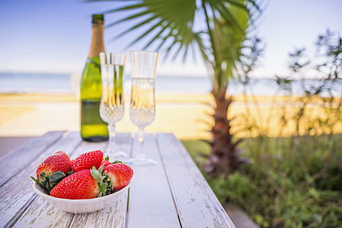 USA, Texas, Bowl of strawberries and champagne on beach with palm tree - ABAF000616