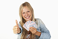 Portrait of teenage girl playing cards and showing thumbs up, smiling - WWF002472