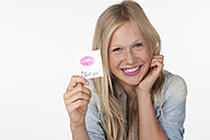 Teenage girl holding a piece of paper with lipstick imprint, smiling - WWF002478