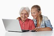 Senior woman and teenage girl using laptop, smiling - WWF002490