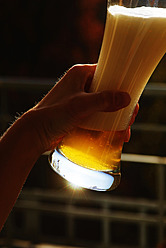 Germany, Bavaria, Human hand holding wheat beer glass, close up - JTF000266