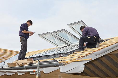 Europe, Germany, Rhineland Palatinate, Workers installing roof windows - CSF016104