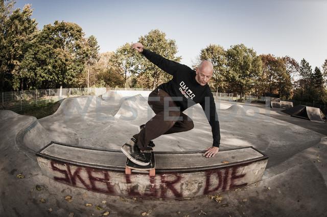 Germany, North Rhine Westphalia, Duesseldorf, Mature man jumping with skateboard - KJF000180