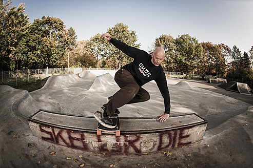 Germany, North Rhine Westphalia, Duesseldorf, Mature man jumping with skateboard - KJF000180