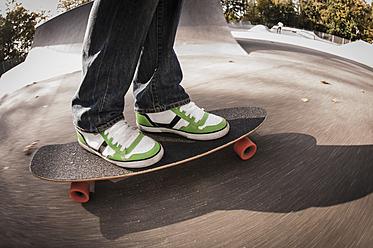 Germany, North Rhine Westphalia, Duesseldorf, Mature man standing on skateboard - KJF000181