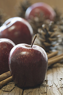 Apples, cinnamon sticks and pine cones for christmas on table - ASF004728