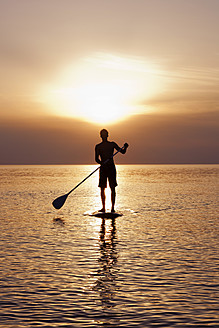 Germany, Schleswig Holstein, Man on stand up paddle board on Baltic sea - DBF000220