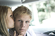 Germany, Duesseldorf, Woman kissing man in car, close up - MF000447
