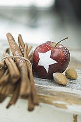 Christmas apple with snow star, cinnamon sticks and almonds on table - ASF004753