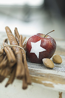 Christmas apple with snow star, cinnamon sticks and almonds on table - ASF004753