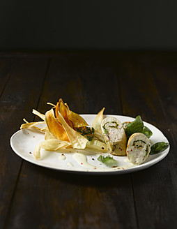 Plate of chicken roulade with chips on wooden table, close up - KSW001015