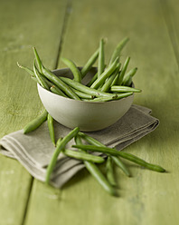 Bowl of green beans on wooden table, close up - KSWF001017