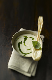 Bowl of potato soup with pesto and puff pastry spoon on wooden table, close up - KSW001023