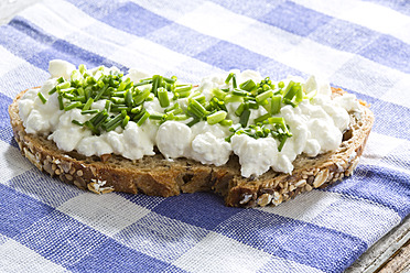 Cottage cheese, butter and chives on whole grain bread, close up - MAEF005628